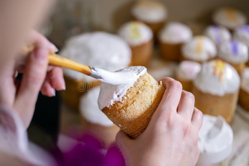 Хлебопек покрывает торты пасхи с белизной яйца и сахаром замороженности стоковая фотография rf