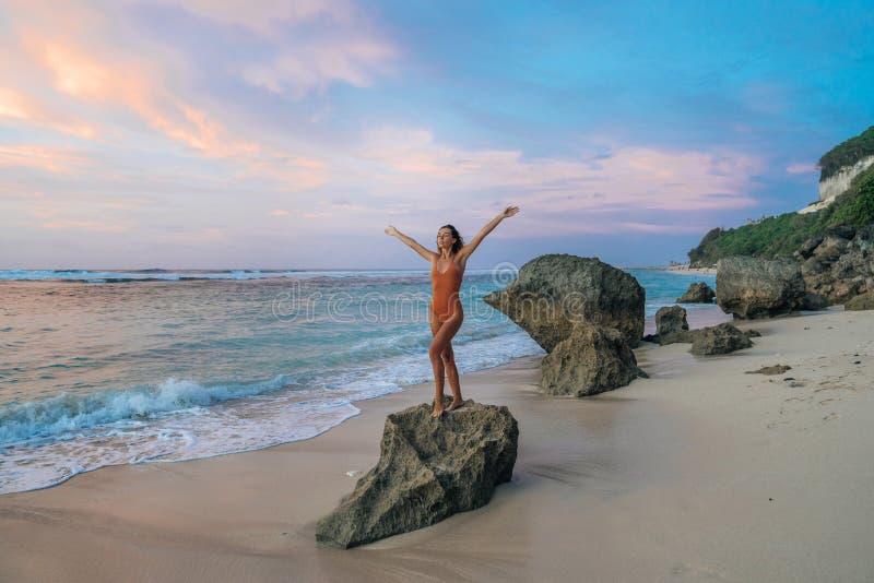 Худенькая женщина с поднятыми руками представляя на большом камне на пляже океаном во время красивого захода солнца стоковые изображения