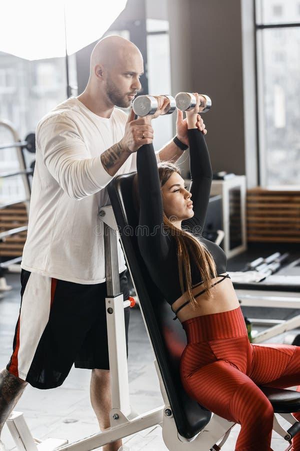 Худенькая славная девушка делает жим лежа гантели вверх по сидеть на стенде пока атлетический человек обеспечивает ее в современн стоковое изображение