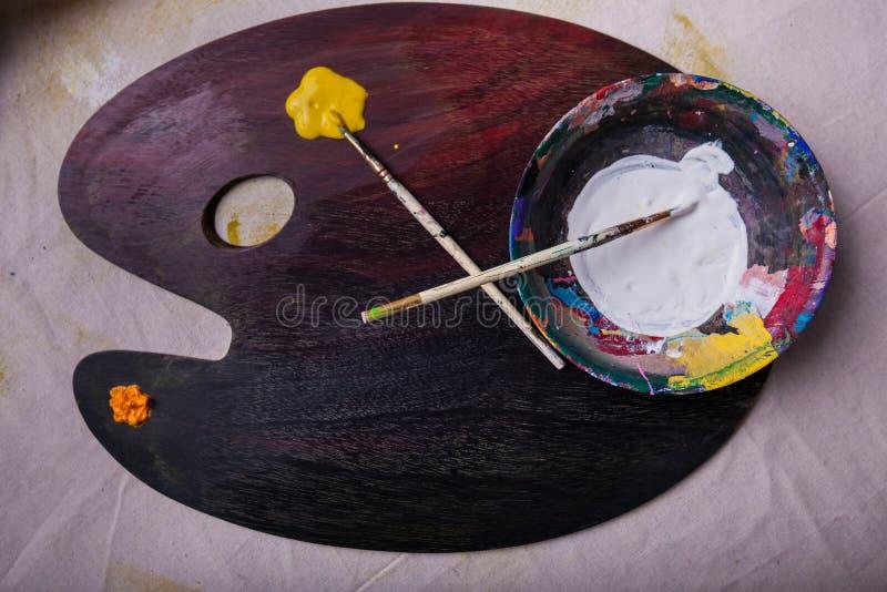 Художники обзора красят смешивая paintbrushes палитры 2 во влажной краске стоковые фото