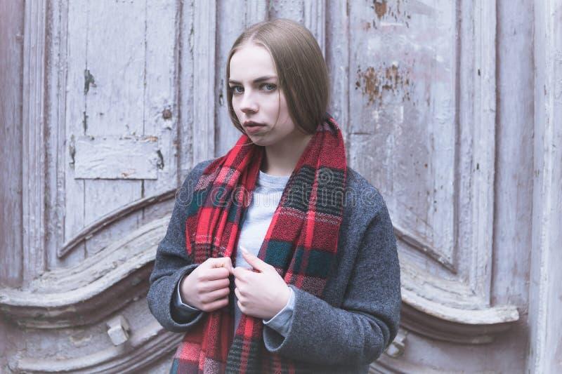 Холодный портрет молодой обиденной привлекательной девушки в пальто и красном шарфе в холодном сезоне на предпосылке старой стоковые изображения