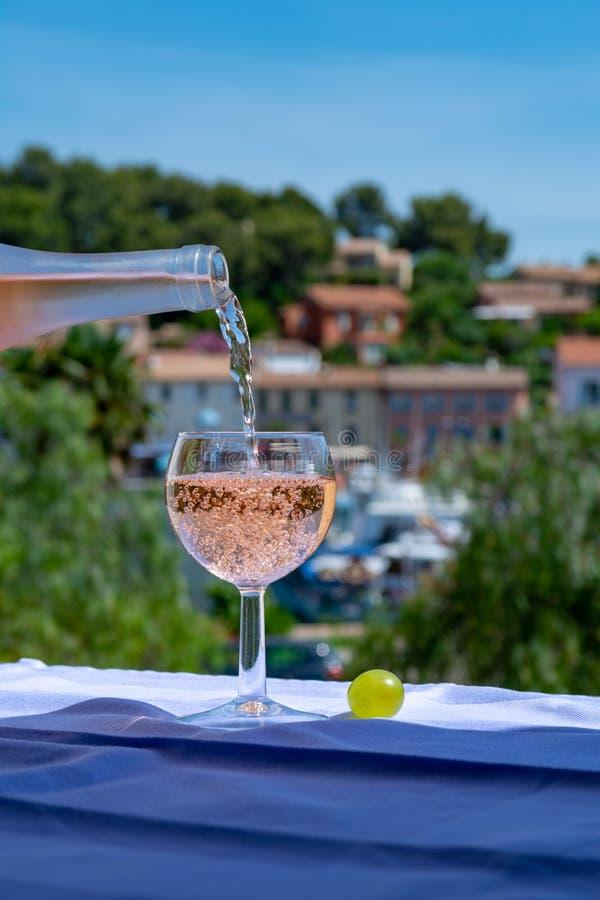 Холод официанта лить розовое вино на на открытом воздухе террасе кафа в Провансали, Франции стоковая фотография rf