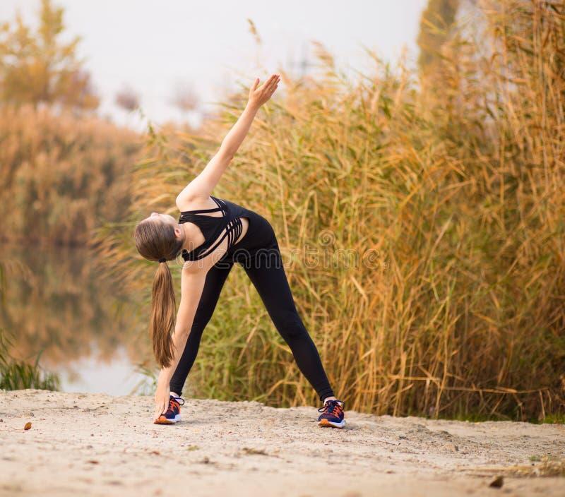 Ход женщины в женщине здорового lifestyleYoung леса падения осени sportive делая тренировки в осени Протягивать спортсменки стоковые фотографии rf
