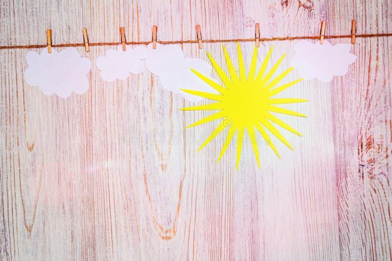 Хорошая погода, яркая концепция солнечного дня Облака и солнце от бумаги прикрепленной с зажимками для белья скопируйте космос стоковое изображение