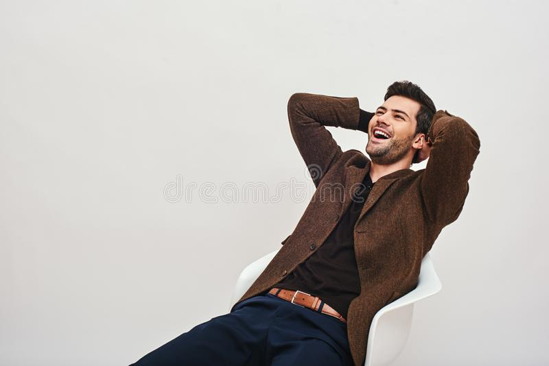Хороший смех излечивает много повреждения Стильный темн-с волосами бизнесмен сидя на стуле, полагаться назад и смеяться стоковые изображения rf