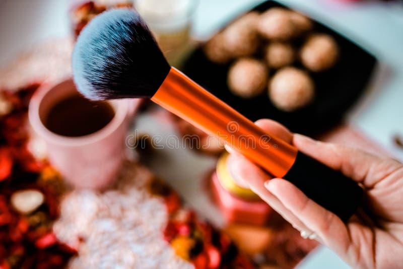 Щетка макияжа в женской руке руки Закройте вверх по взгляду на запачканной предпосылке взгляд Перв-персоны стоковые фото
