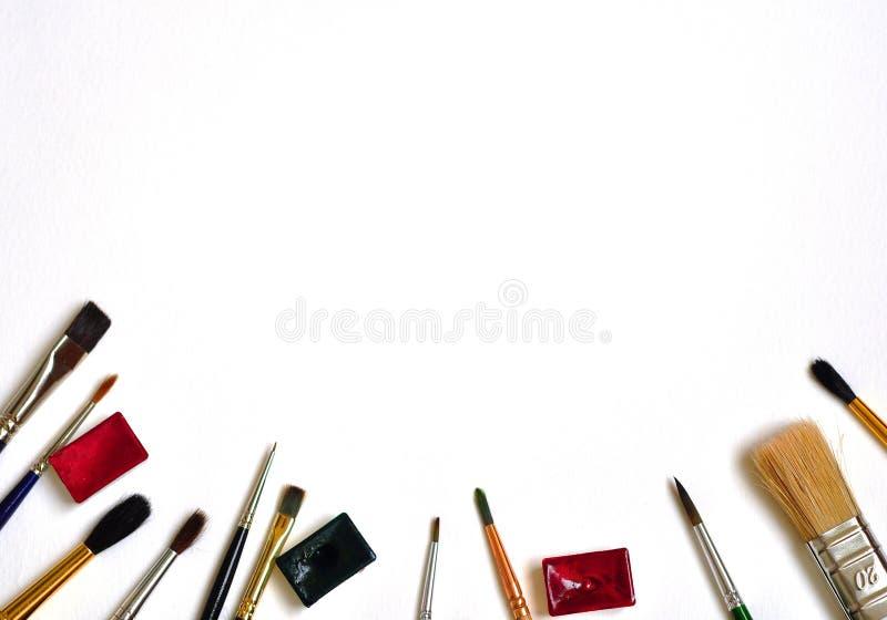 Щетки и краски искусства на белой предпосылке Плоское положение, взгляд сверху, космос экземпляра стоковое изображение rf