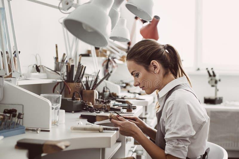 Работать весь день Взгляд со стороны молодого женского ювелира сидя на ее мастерской ювелирных изделий и держа в инструментах юве стоковое фото