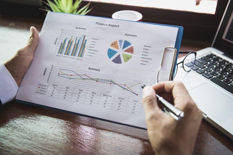 Работа бизнесмена на статистике и диаграммах дела, бизнесмене держа ручку работает с документами диаграммы, диаграммой фондовой б стоковое изображение
