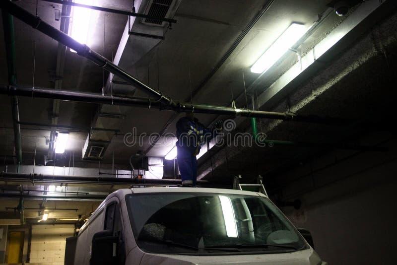 Работа промышленная чистой нечистот, трубопровода, вентиляции на основании автомобиля в здании профессионал стоковая фотография