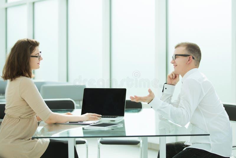 2 работника обсуждают что-то сидя на таблице офиса стоковое изображение rf