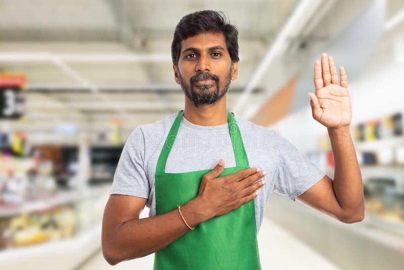 Работник гипермаркета делая присягу стоковая фотография