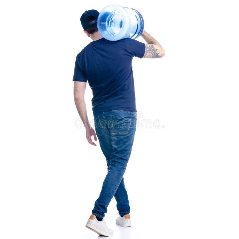 Работник доставляющий покупки на дом воды в голубой футболке и крышка идут идут стоковое изображение