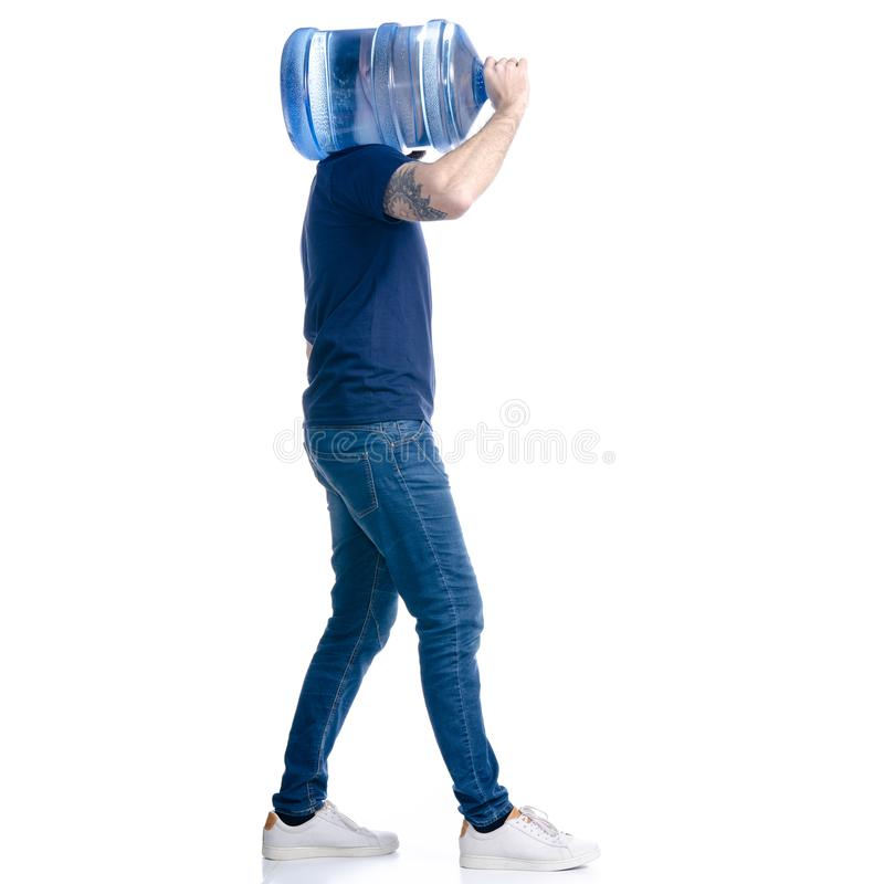 Работник доставляющий покупки на дом воды в голубой футболке и крышка идут идут стоковые фото