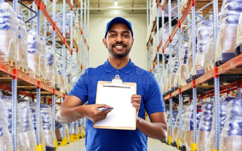 Работник доставляющий покупки на дом или работник склада с доской сзажимом для бумаги стоковое изображение rf