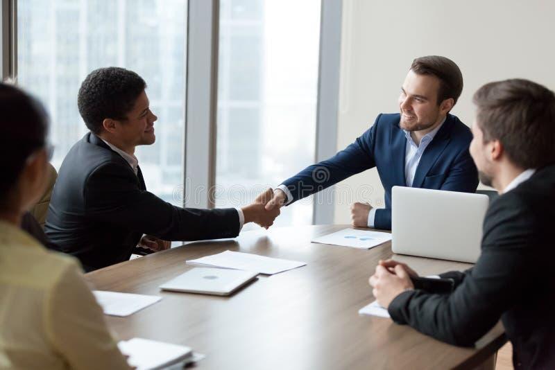Работник handshaking CEO (главный исполнительный директор) компании африканский на корпоративной групповой встрече стоковые фотографии rf
