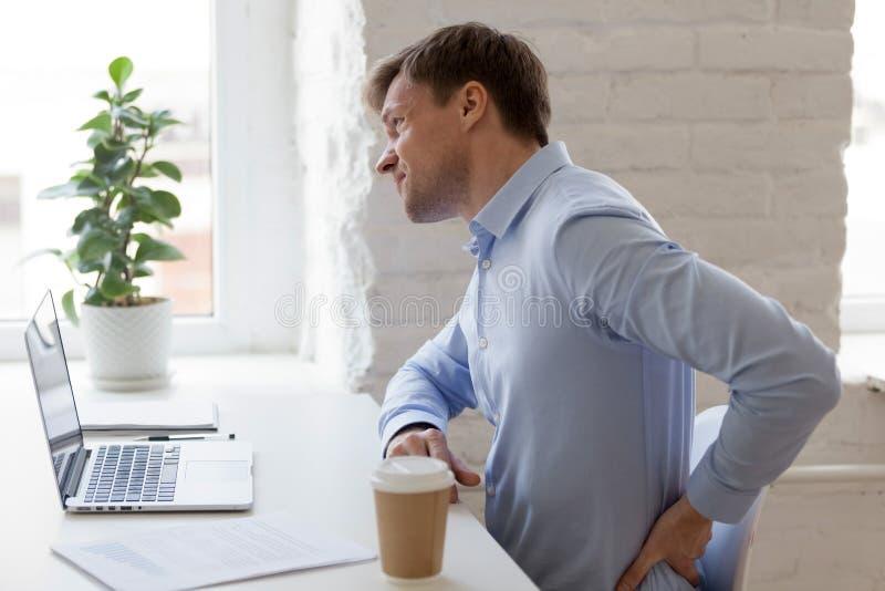 Работник офиса имея сильную более низкую боль в спине стоковые изображения rf