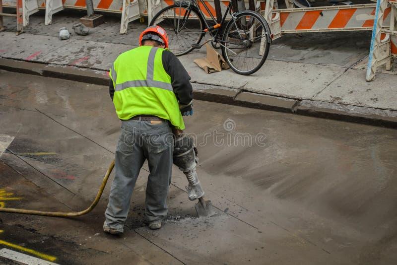 Рабочий-строитель Jackhammer в жилете безопасности стоковое изображение