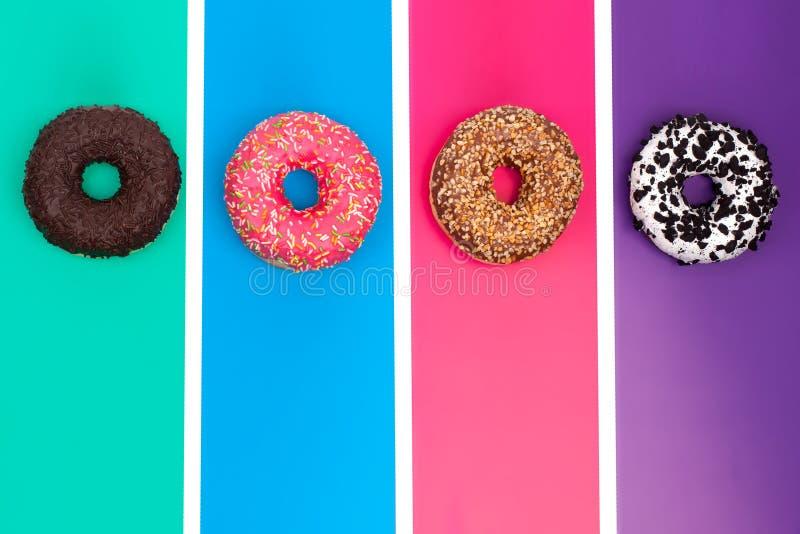 4 различных donuts на ярком пестротканом взгляде сверху предпосылки стоковое изображение rf