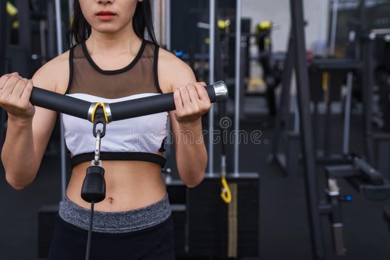 Разминка тренировки женщины фитнеса с кабелем тренировк-машины в спортзале фитнеса уклад жизни принципиальной схемы здоровый стоковое изображение rf