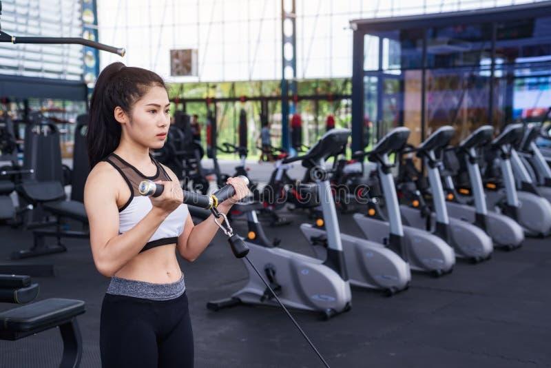 Разминка тренировки женщины фитнеса с кабелем тренировк-машины в спортзале фитнеса уклад жизни принципиальной схемы здоровый стоковые фотографии rf