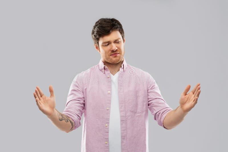 Раздражанный размер показа молодого человека что-то стоковое фото rf