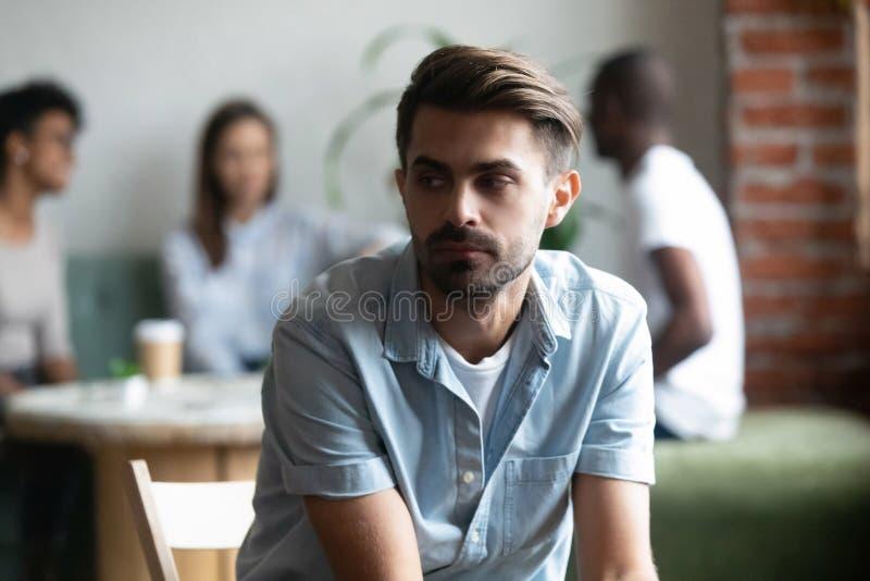 Разочарованный сиротливый застенчивый парень сидя врозь других подростки стоковое фото rf