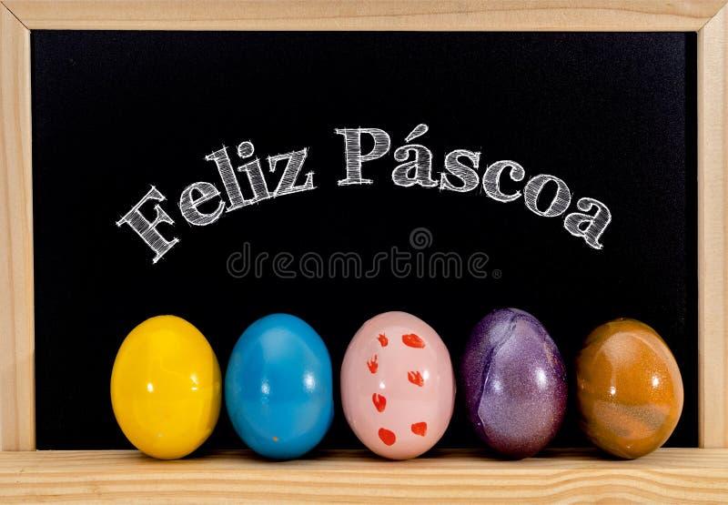 Рамка пасхи с покрашенными яйцами и доской Счастливая пасха в белом меле Счастливая пасха на португальском: scoa ¡ pà feliz стоковое изображение