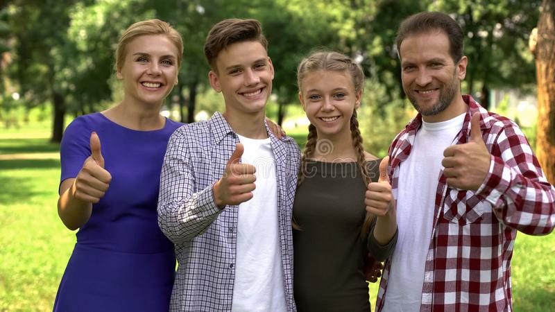 Радостные члены семьи наслаждаясь выходными в парке и показывая большие пальцы руки вверх в камеру стоковое изображение