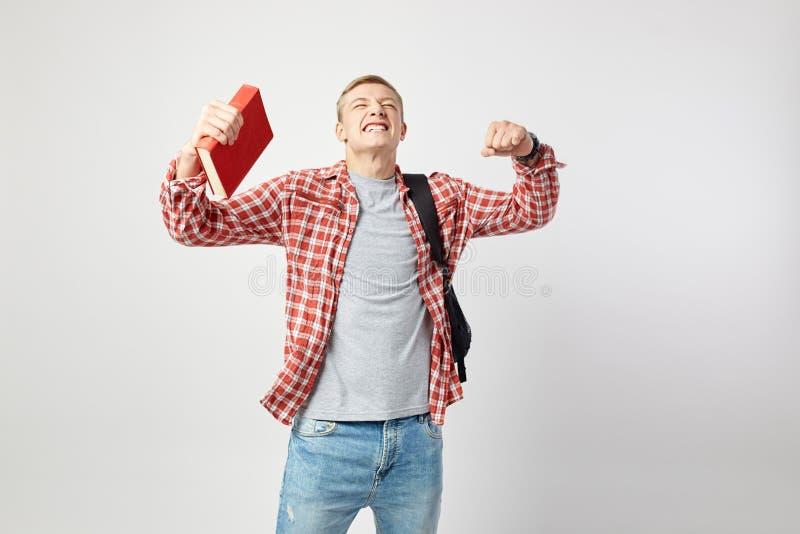 Радостный белокурый парень с черным рюкзаком на его плече одетом в белой футболке, красной checkered рубашке и владениях джинсов стоковые фотографии rf