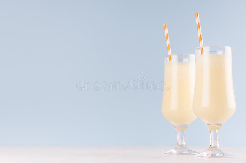 Радостный красочный десерт апельсинов молока с striped соломой на современной элегантной голубой предпосылке цвета стоковые изображения