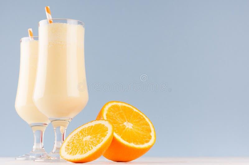 Радостный красочный десерт с сочными кусками, striped солома апельсинов молока на современной элегантной голубой предпосылке цвет стоковое изображение rf