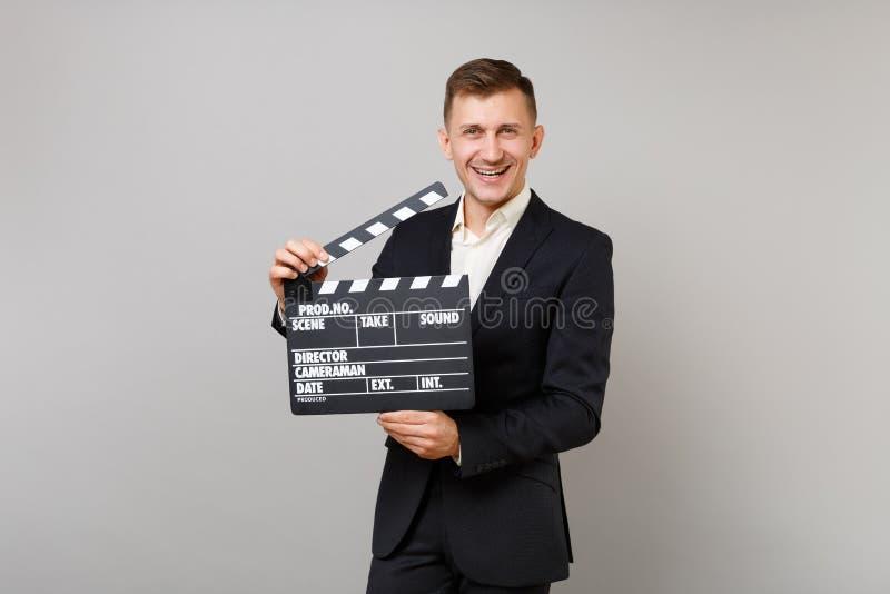 Радостный молодой бизнесмен в классическом черном костюме, рубашке держа классическое черное clapperboard создания фильма изолиро стоковая фотография