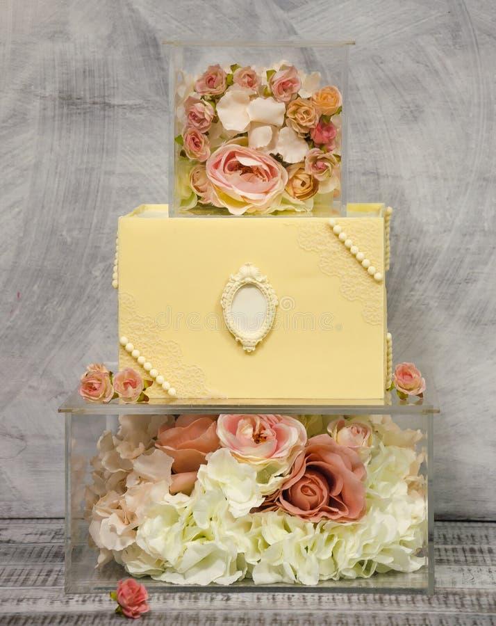 Расположенный ярусами свадебный пирог шоколада восхитительные 3 на стеклянной украшенной коробке с розами стоковая фотография rf