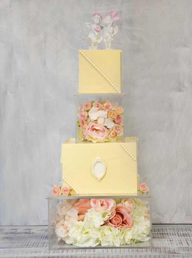 Расположенный ярусами свадебный пирог шоколада восхитительные 4 на стеклянной украшенной коробке с розами стоковые фотографии rf