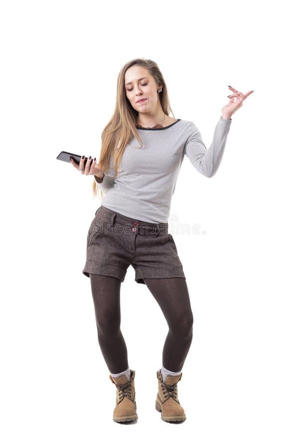 Расслабленные жизнерадостные танцы молодой женщины с музыкой закрытых глаз слушая на громкоговорителе мобильного телефона стоковое фото rf