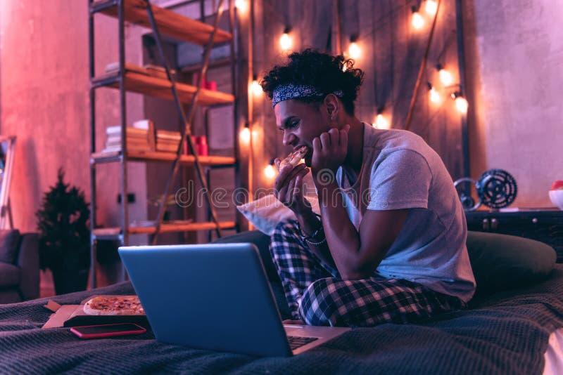 Расслабленный Афро-американский мальчик сидя на кровати и есть пиццу пока смотрящ фильм стоковые фото