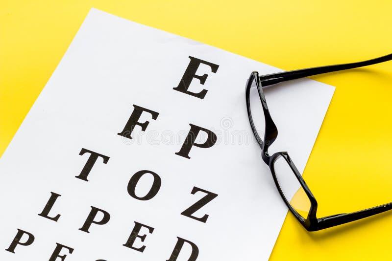 Рассмотрение глаза Диаграмма и стекла теста зрения на желтой предпосылке стоковая фотография rf