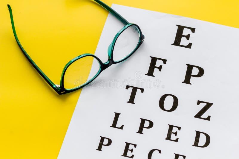 Рассмотрение глаза Диаграмма и стекла теста зрения на желтой предпосылке стоковое фото rf