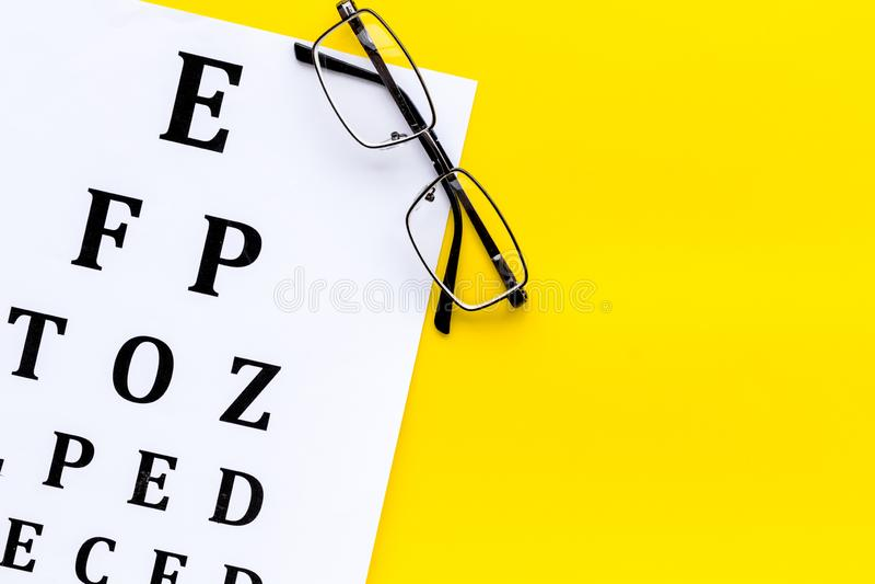 Рассмотрение глаза Диаграмма и стекла теста зрения на желтом космосе экземпляра взгляда сверху предпосылки стоковое фото rf