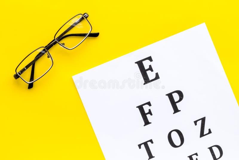 Рассмотрение глаза Диаграмма и стекла теста зрения на желтом космосе экземпляра взгляда сверху предпосылки стоковые изображения rf