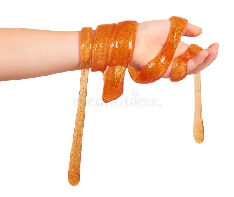 ребенк играя оранжевый шлам с рукой, прозрачной игрушкой стоковая фотография rf