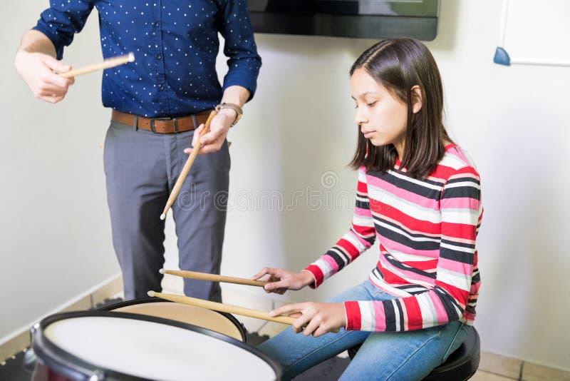 Ребенк с барабанчиком учителя практикуя в музыкальном классе стоковые фото