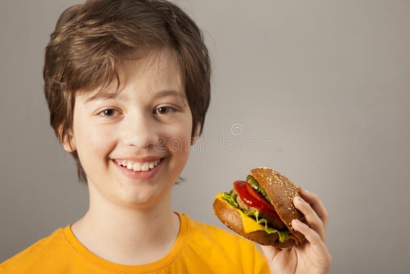 Ребенок ест бургер на серой предпосылке Мальчик с гамбургером стоковое фото