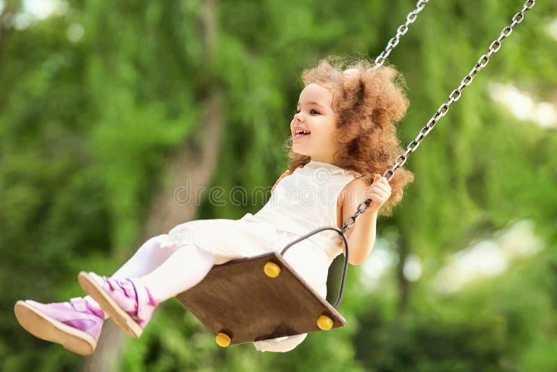 Ребенок отбрасывая на качании на спортивной площадке в парке стоковое изображение rf