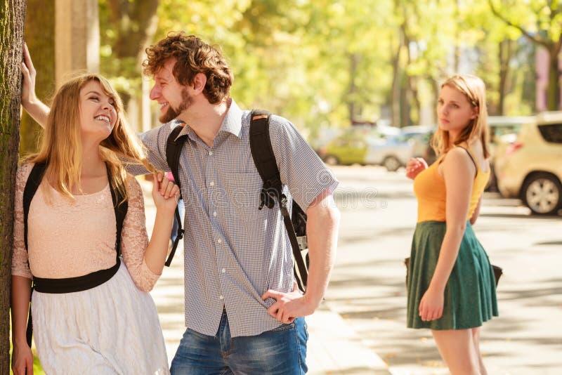 Ревнивая девушка смотря flirting пар внешних стоковая фотография