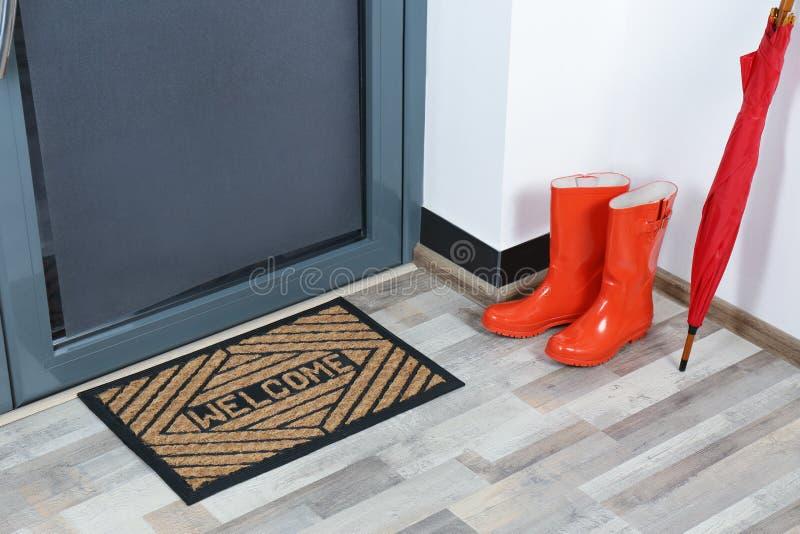 Резиновые ботинки, зонтик и циновка около двери стоковое фото rf
