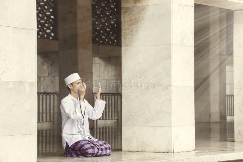Религиозный мусульманский человек моля к Аллаху стоковая фотография rf