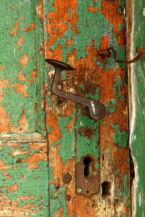 Ржавые doorknob и защелка на старой выдержанной зеленой двери стоковая фотография