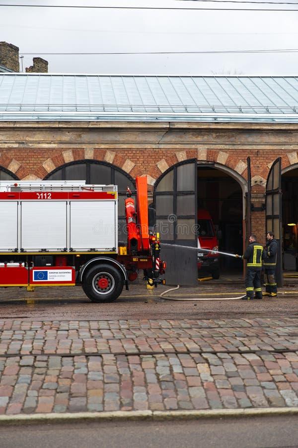 РИГА, ЛАТВИЯ - 16-ОЕ МАРТА 2019: Пожарная машина очищенный - водитель моет тележку пожарного на depo - Van в гараже стоковое изображение rf